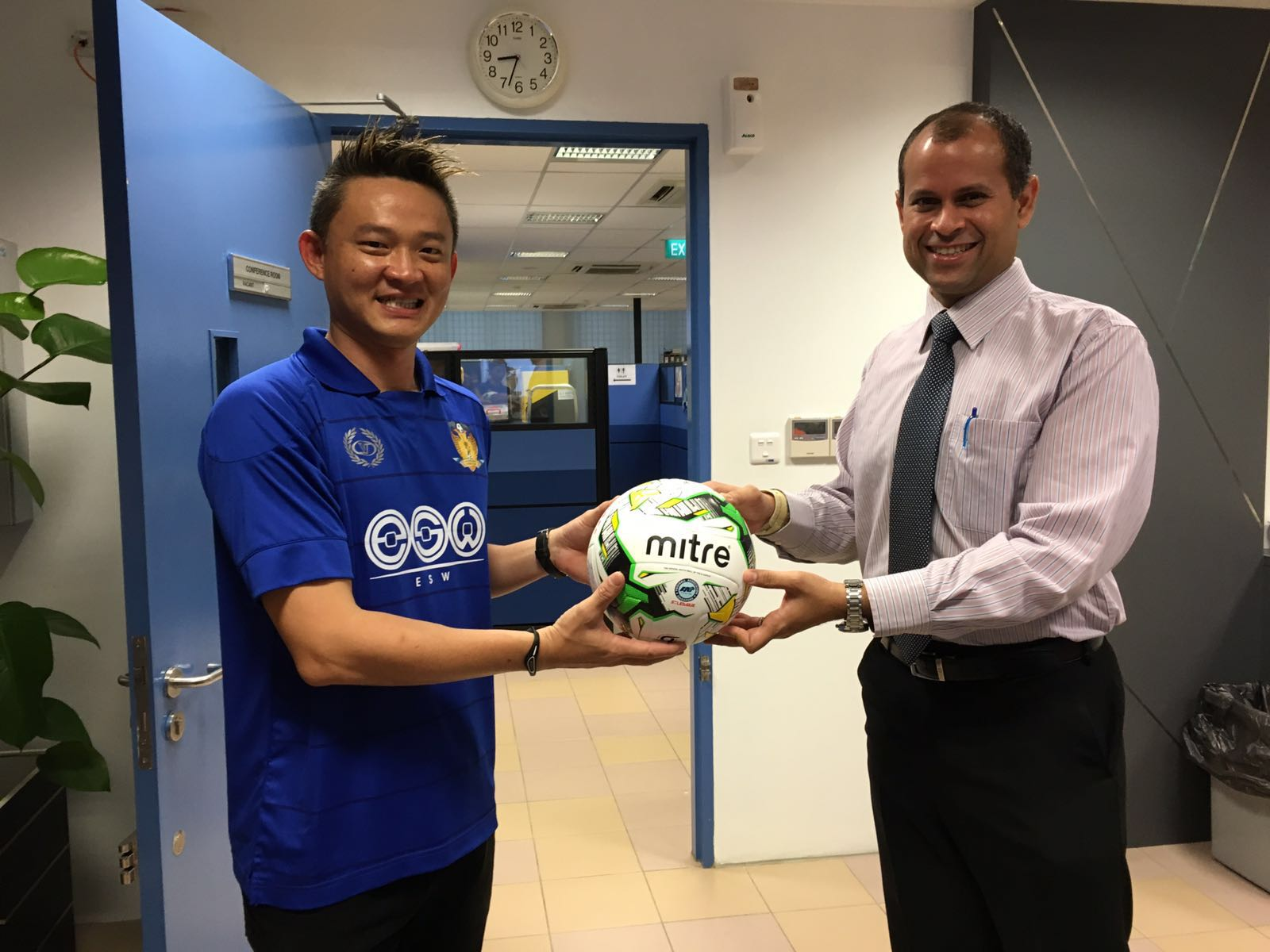 Matthew Tay presenting a signed Mitre football to Principal Mr Minjoot.
